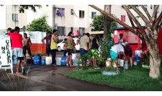 After electrical outage, residents line up to get water in a Macapá housing